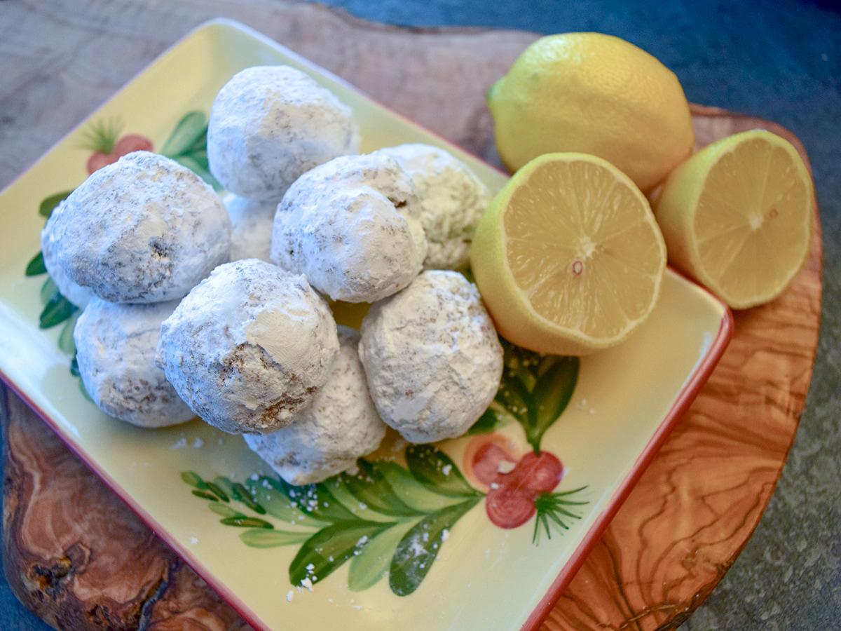 lemon cookies with powdered sugar on plate next to lemons