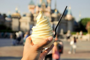 Pineapple soft served in a cup held in front of Disneyland Castle- Disney Dole Whip