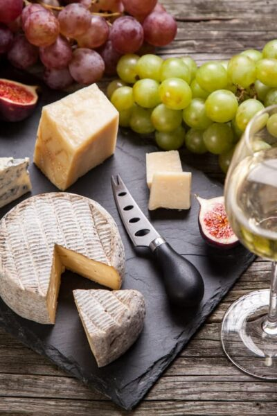 wine glasses and cheese platter with fruit