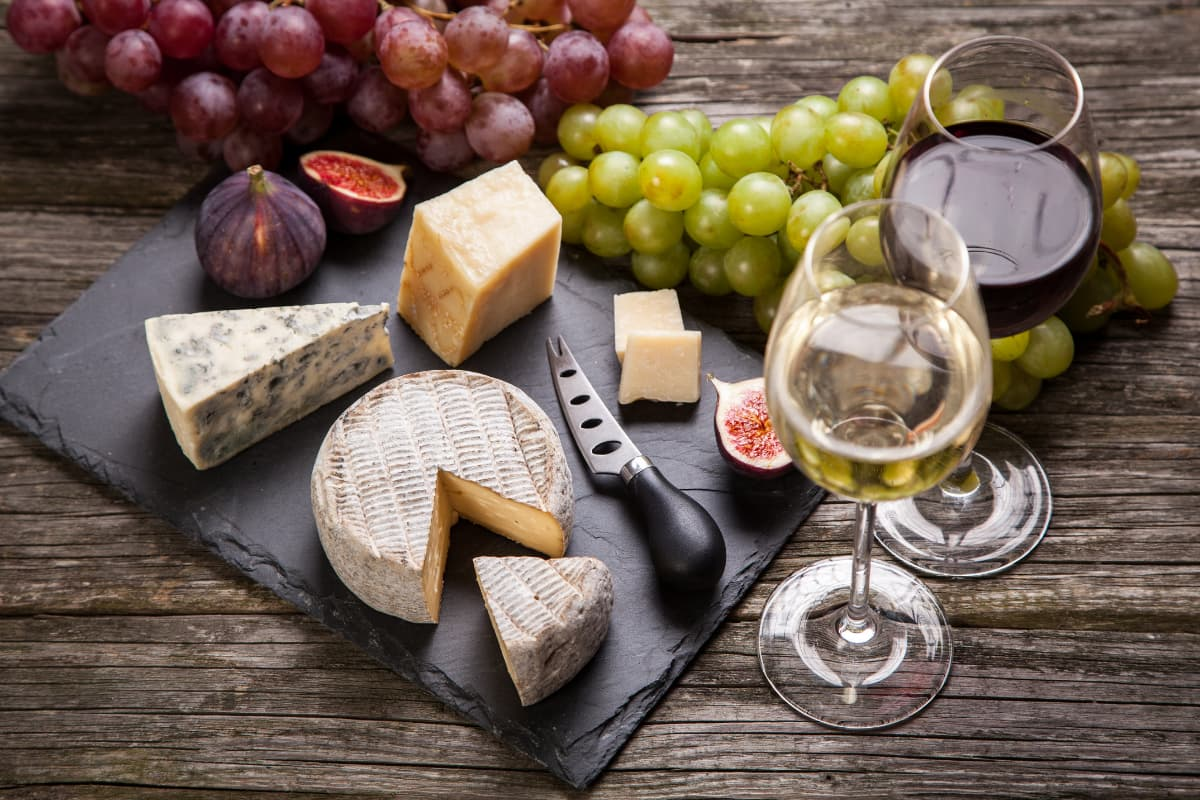 wine glasses and cheese platter with grapes