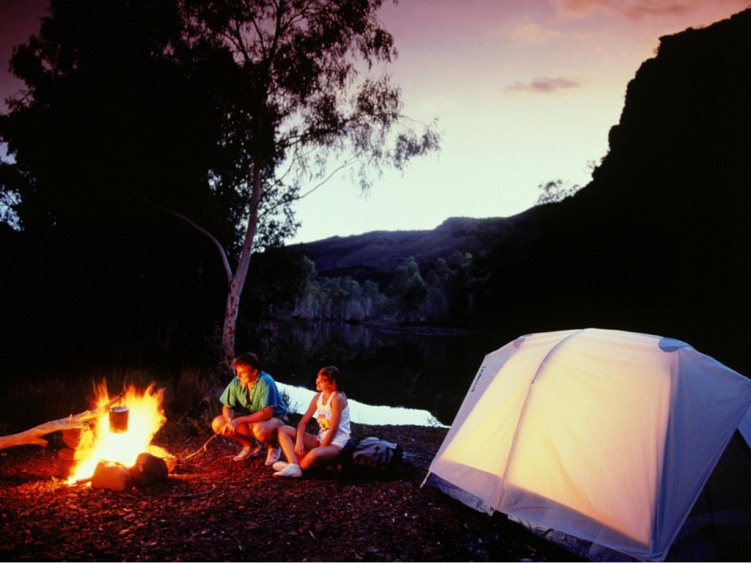 couple sitting at a campfire, camping