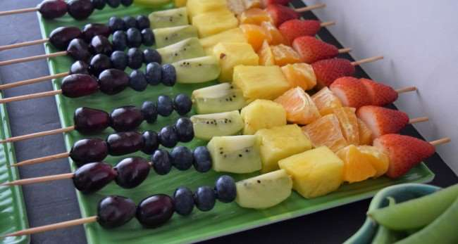 Rainbow Fruit Skewers with red grapes, blueberries, kiwi, pineapple, orange, and strawberry