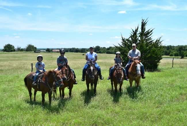 family o n horseback on a grassy field