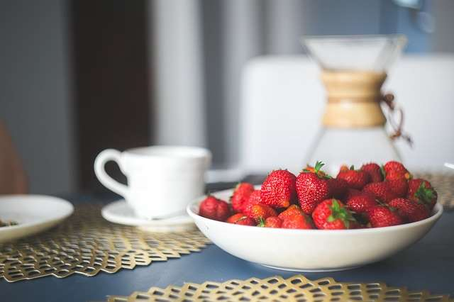 strawberries in a bowl, coffee cup