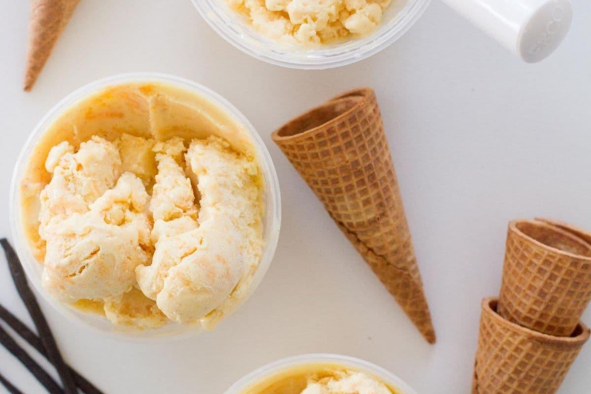 peach ice cream in cup aside sugar cones