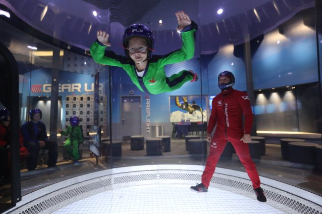Girl and instructor inside a wind tunnel at iFly