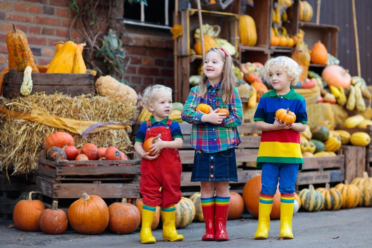 children with pumpkins at a farm stand