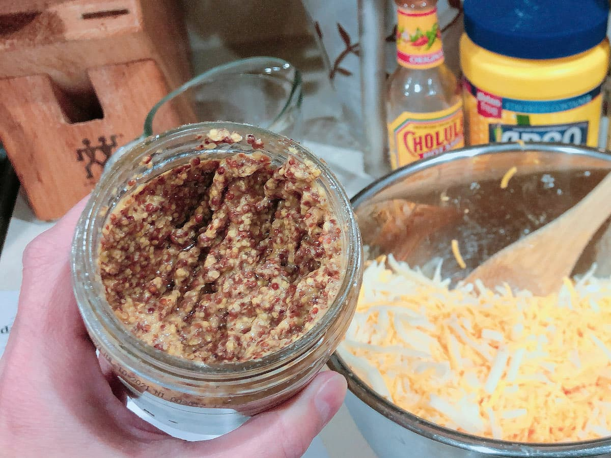 whole grain mustard in jar next to shreadded cheese bowl