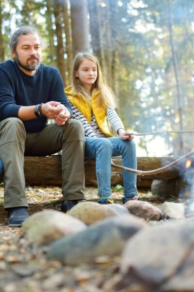 father and daughters roasting marshmallows over fire