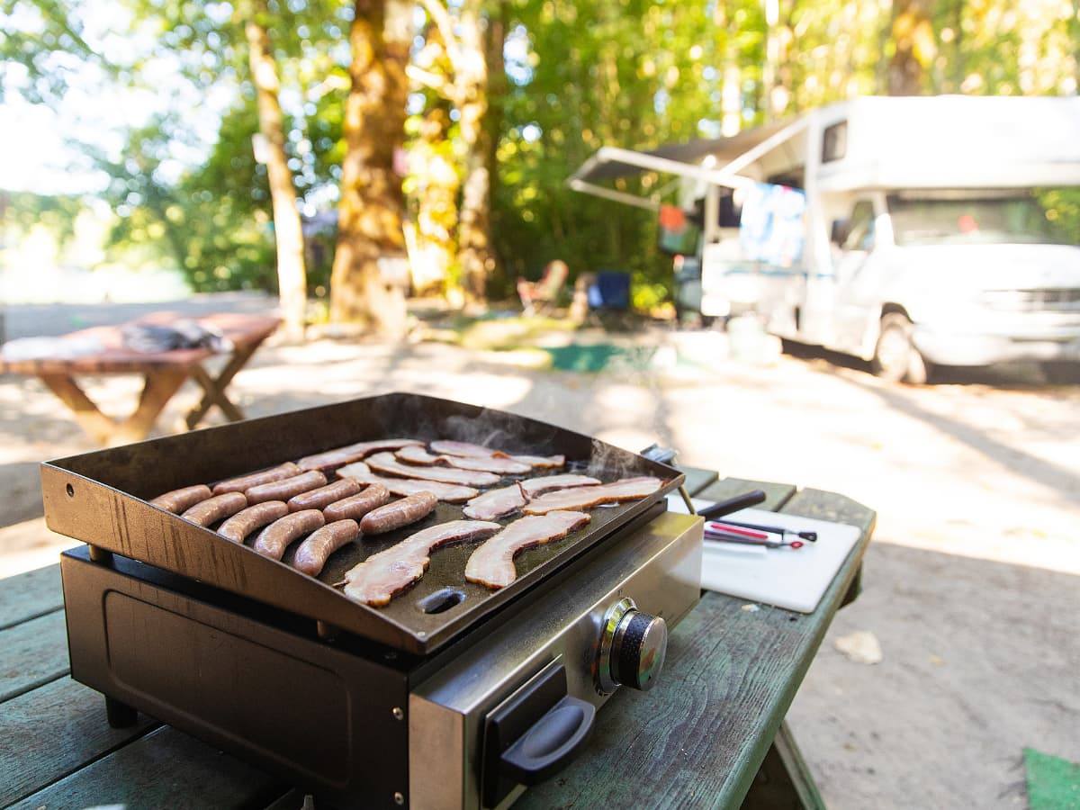flattop griddle cooking breakfast outdoors in front of RV
