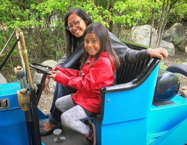 Girl and woman riding an antique cars at Silverwood Theme Park in Athol Idaho