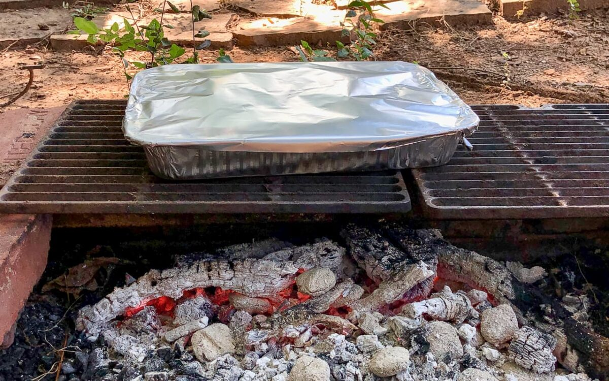 foil covered pan over campfire coals