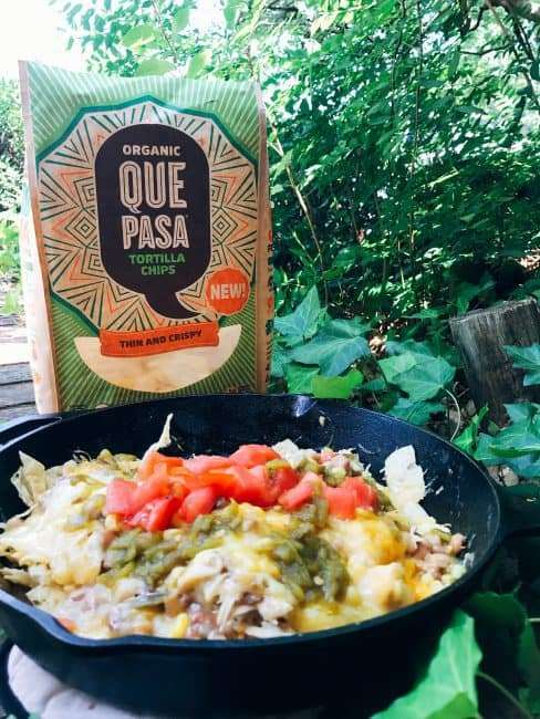 Make anywhere Campfire Nachos with green Chile chicken, beans, and corn. made with Que Past Organic Tortilla Chips