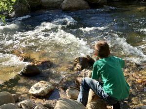 Creek running with boy alongside
