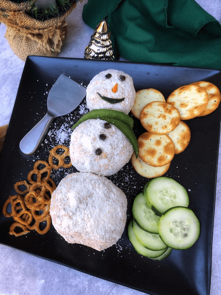 Holiday appetizers should be this fun! This adorable snowman is a cheeseball made with seasoned cream and Cheddar cheese.  #holidayappetizer #cheeseman #snowman #holidayfood #appetizer #cheeseball