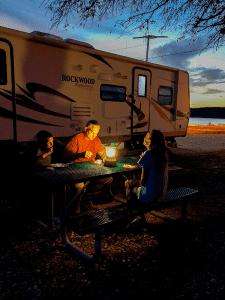 Family eating dinner outdoors by lantern light.