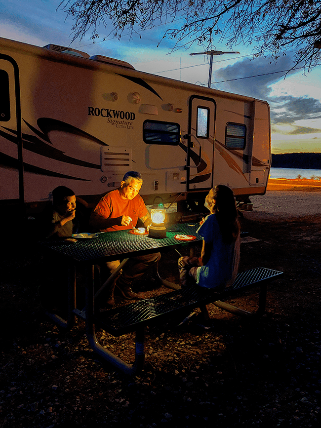 Family eating dinner outdoors by lantern light.