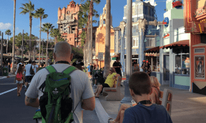 People walking down a street, man is wearing a lightweight backpack