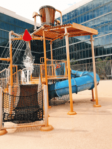 Water play area with a water slide and dump buckets