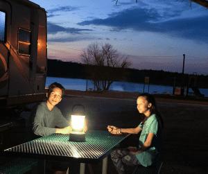 Older children eating outdoors by lantern light