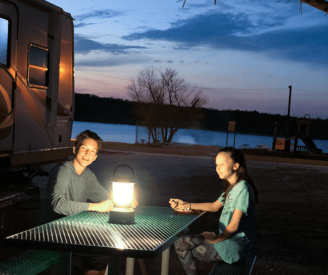 Older children eating outdoors by lantern light