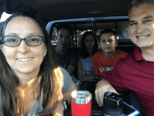 traveling family with forced smiles on the adults and unhappy kids in the backseat