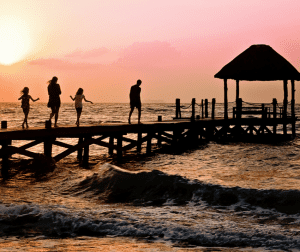 family walking on a pier at sunset - Ever Feel You Need to Recover AFTER Your Family Vacation? Family travel can be stressful, but here are a few tips that helped us make vacations together more enjoyable and less exhausting