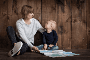 Mother and children looking at a map - Tips to Planning International Travel with Children as a Single Parent - Easy ways to plan your next trip aboard when your partner/spouse is staying home.