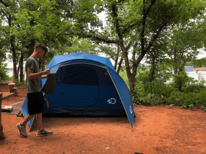 camping tent with teen in front - Ensure Your Next Family Camping Trip is Epic with these Summer Planning Tips