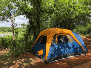 camping tent set in a wooded area. Ensure Your Next Family Camping Trip is Epic with these Summer Planning Tips