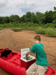 boy grabbing snack from ice cooler - Ensure Your Next Family Camping Trip is Epic with these Summer Planning Tips