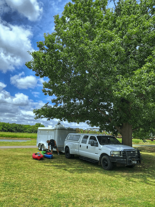 Man at the lake with kayaks and a truck with trailer