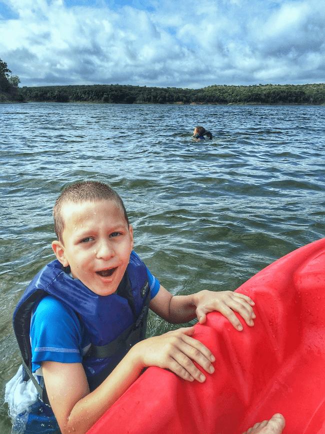 boy swimming kayaking