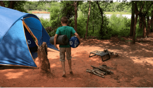 boy holding sleeping bags at camp site