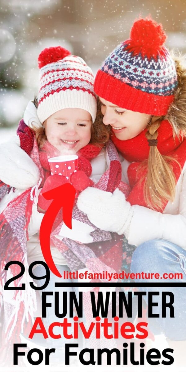 woman and child in snow enjoying hot beverage