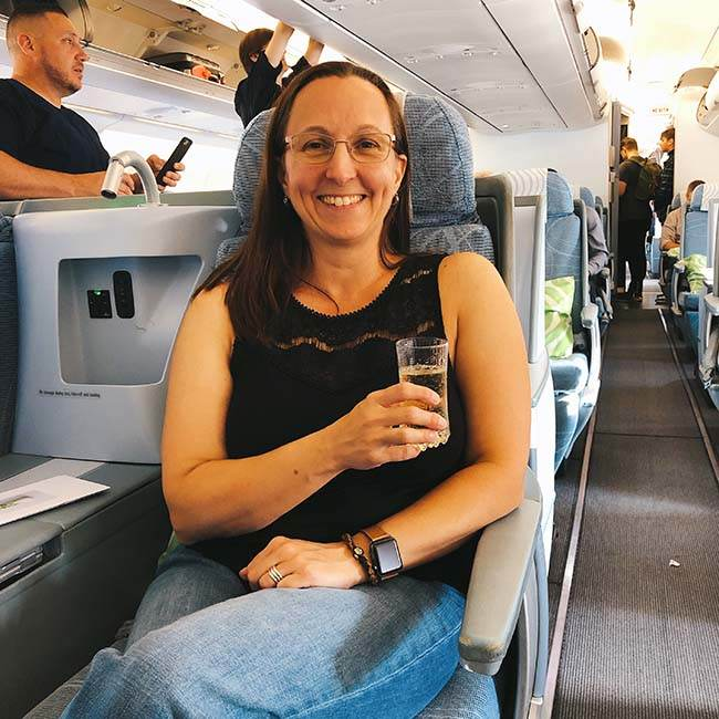 woman in airplane with champagne