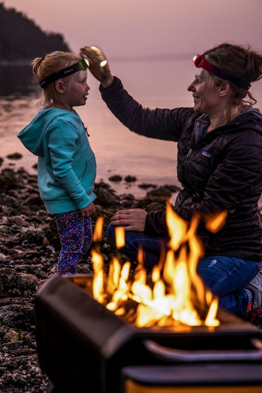 woman and child lakeside in front of fire