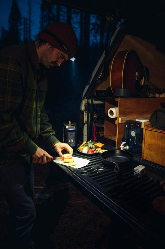 man cooking outdoors at night