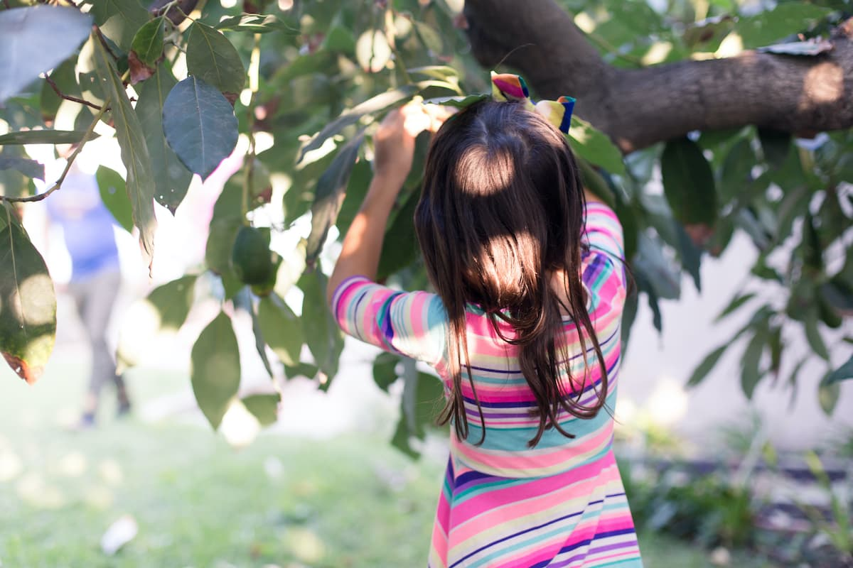 girl outdoors by a tree
