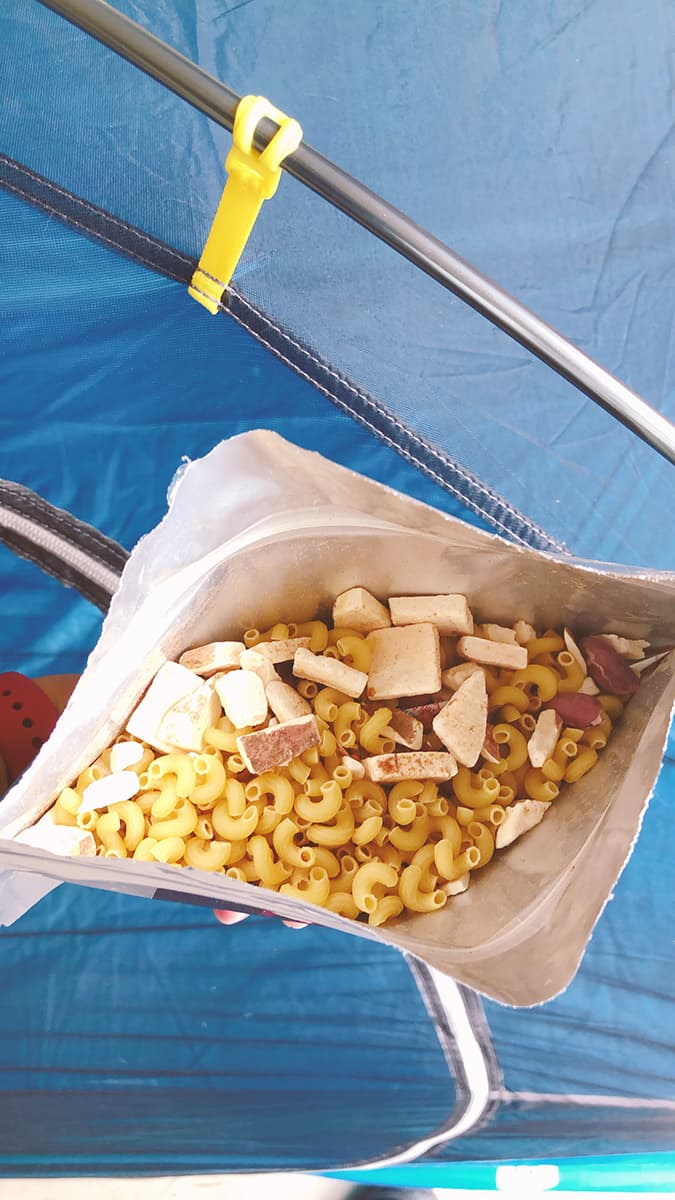Freeze dried pasta and sweet potato in a heat and serve pouch, blue tent in background