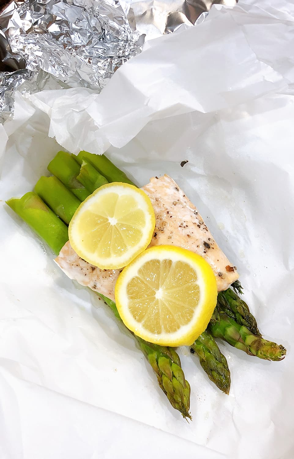 asparagus and salmon with lemon slices on parchment paper