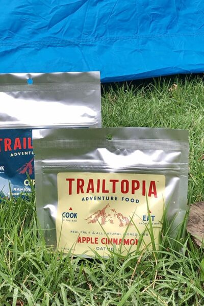 trailtopia camping food pouches, rocket stove, pot, and camping mess kit on the grass