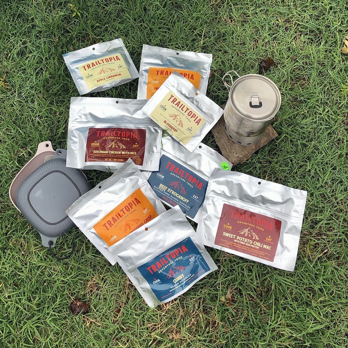 trailtopia freeze-dried camping food pouches on the grass, cooking pot and bowl