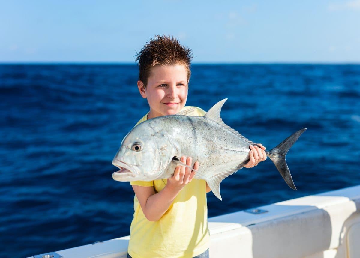boy holding fish, deep sea