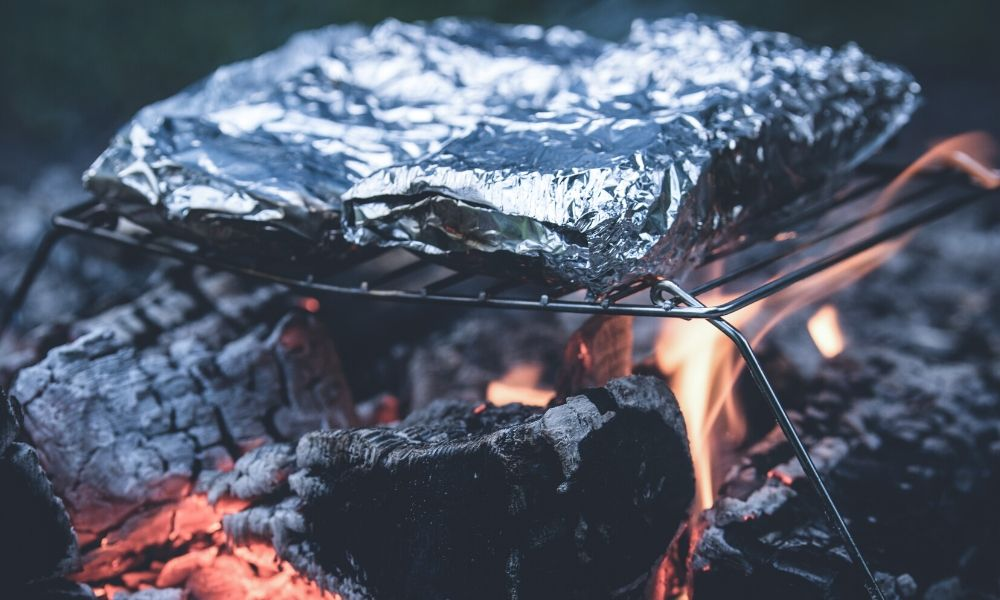 foil packets cooked on grate over campfire