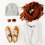 grey beanie, sunglasses, brown circle scarf, brown shoes, and white sweater