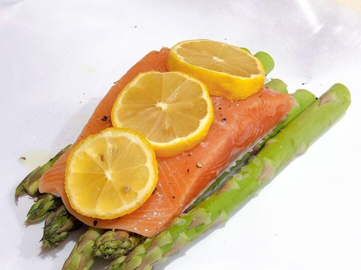 Salmon and asparagus with lemon slices on parchment paper