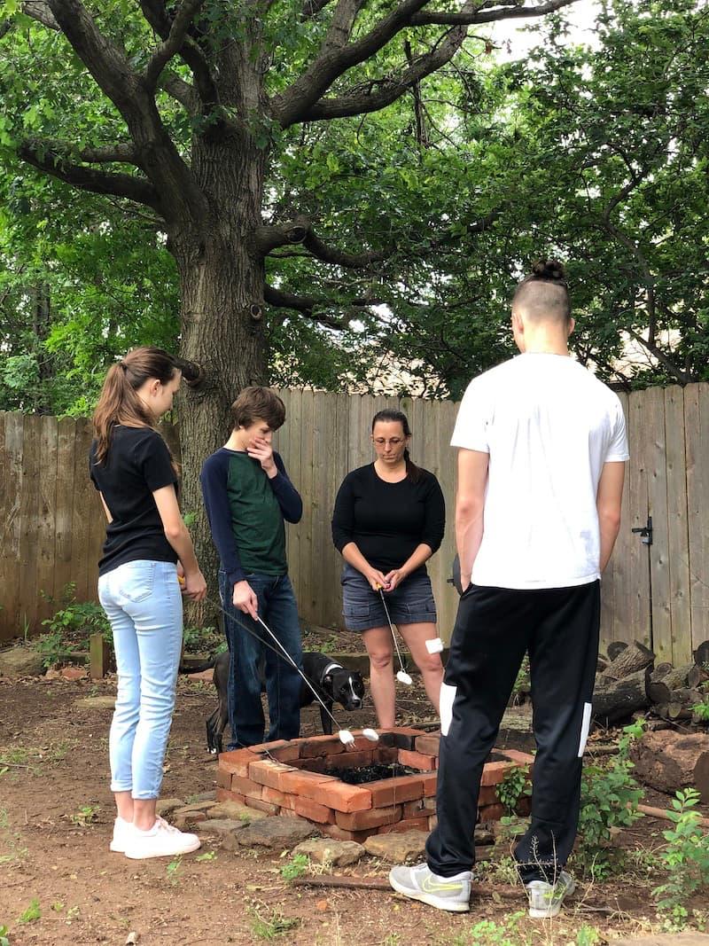 family roasting smores over backyard firepit