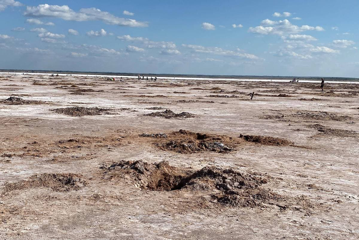 salt plains Oklahoma, people far in the distance, holes foreground from crystal digging