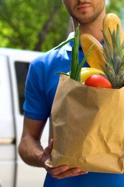 man delivering brown sack of groceries
